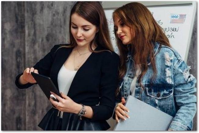 タブレットをのぞきこむ二人の外国人女性