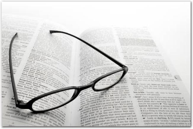 英語の辞書と黒ぶちのレディース用メガネ