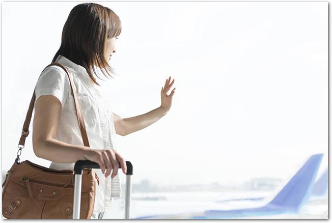 飛行場から窓の外を眺める女性