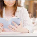 カフェで本を読む笑顔の女性