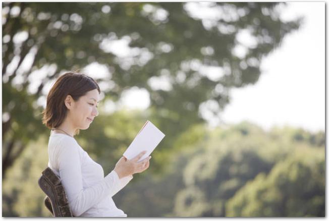 ベンチに座って本を読む女性