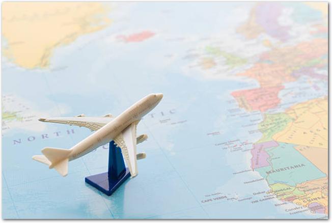 世界地図と飛行機の模型で海外渡航のイメージ