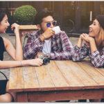 カフェで談笑する日本人女性と外国人カップル